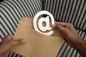 Male hand putting an at sign into an envelope
