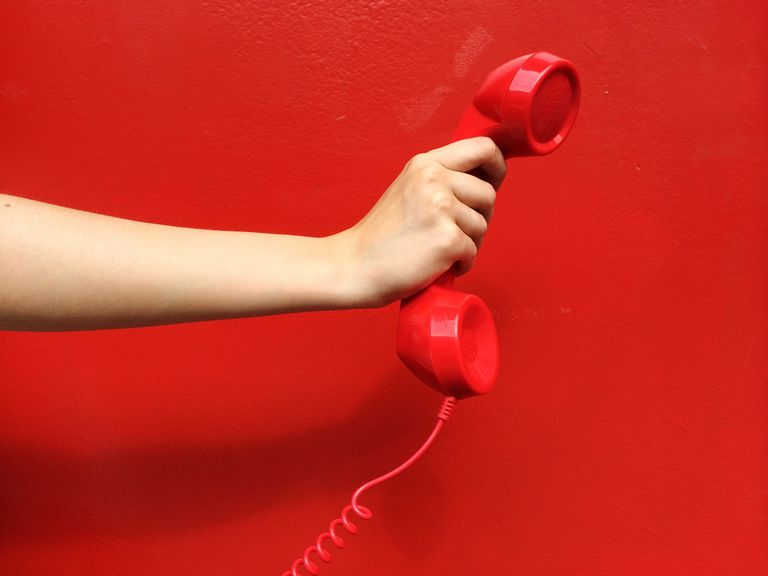 Someone picking up a telephone call on a red landline handset