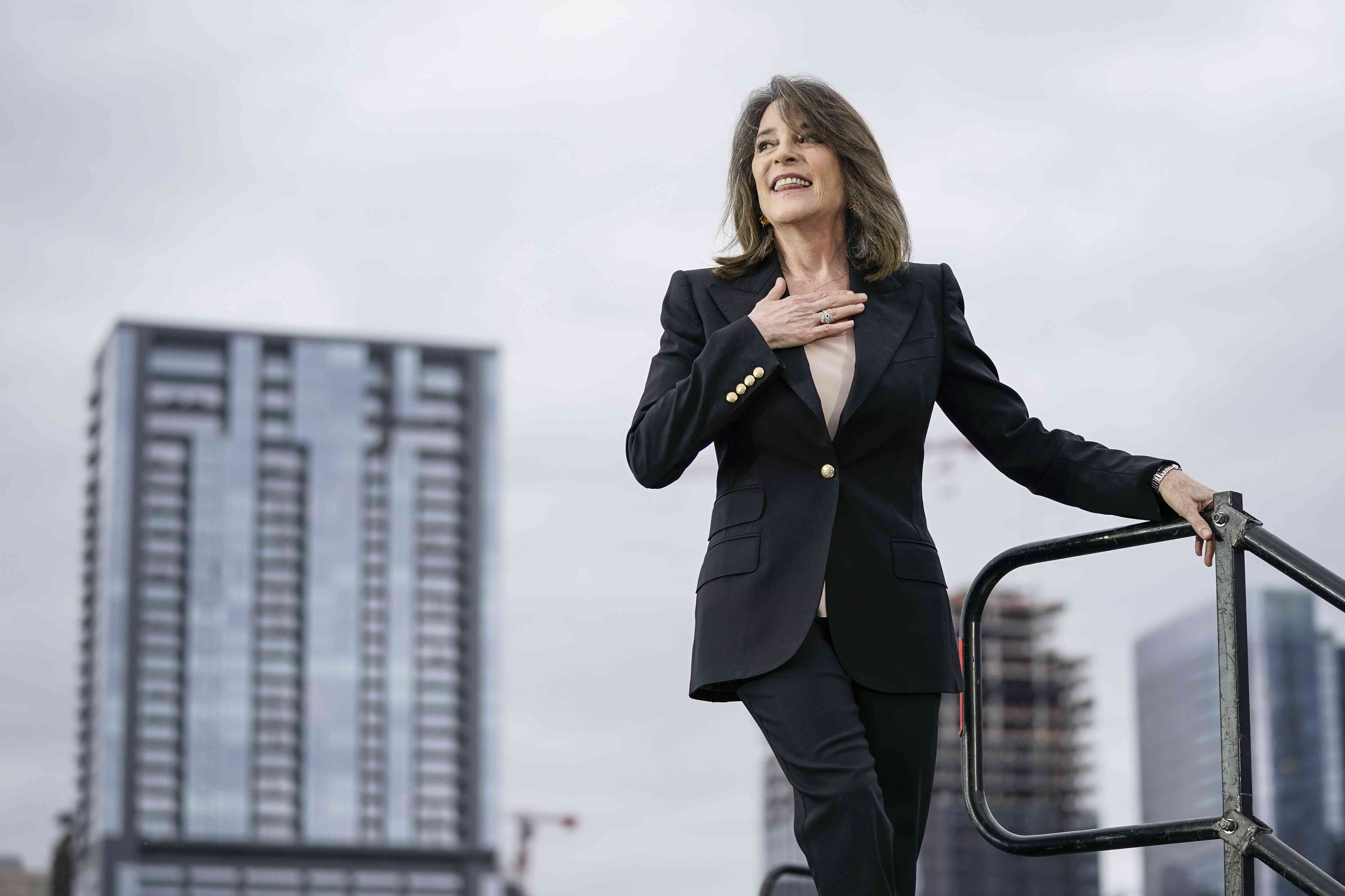Marianne Williamson smiling with her hand over her chest while descending a staircase