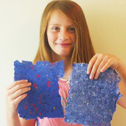 girl holds up handmade blue paper