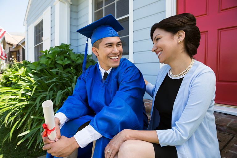 Smiling graduate and mother on front stoop