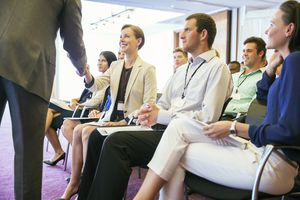 Public speaker shaking hands with people attending seminar