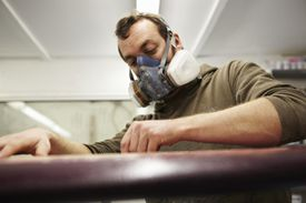 Surfboard glasser wears a gas mask while glassing a surfboard