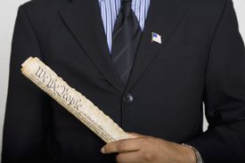 a man holding a rolled up copy of the constitution
