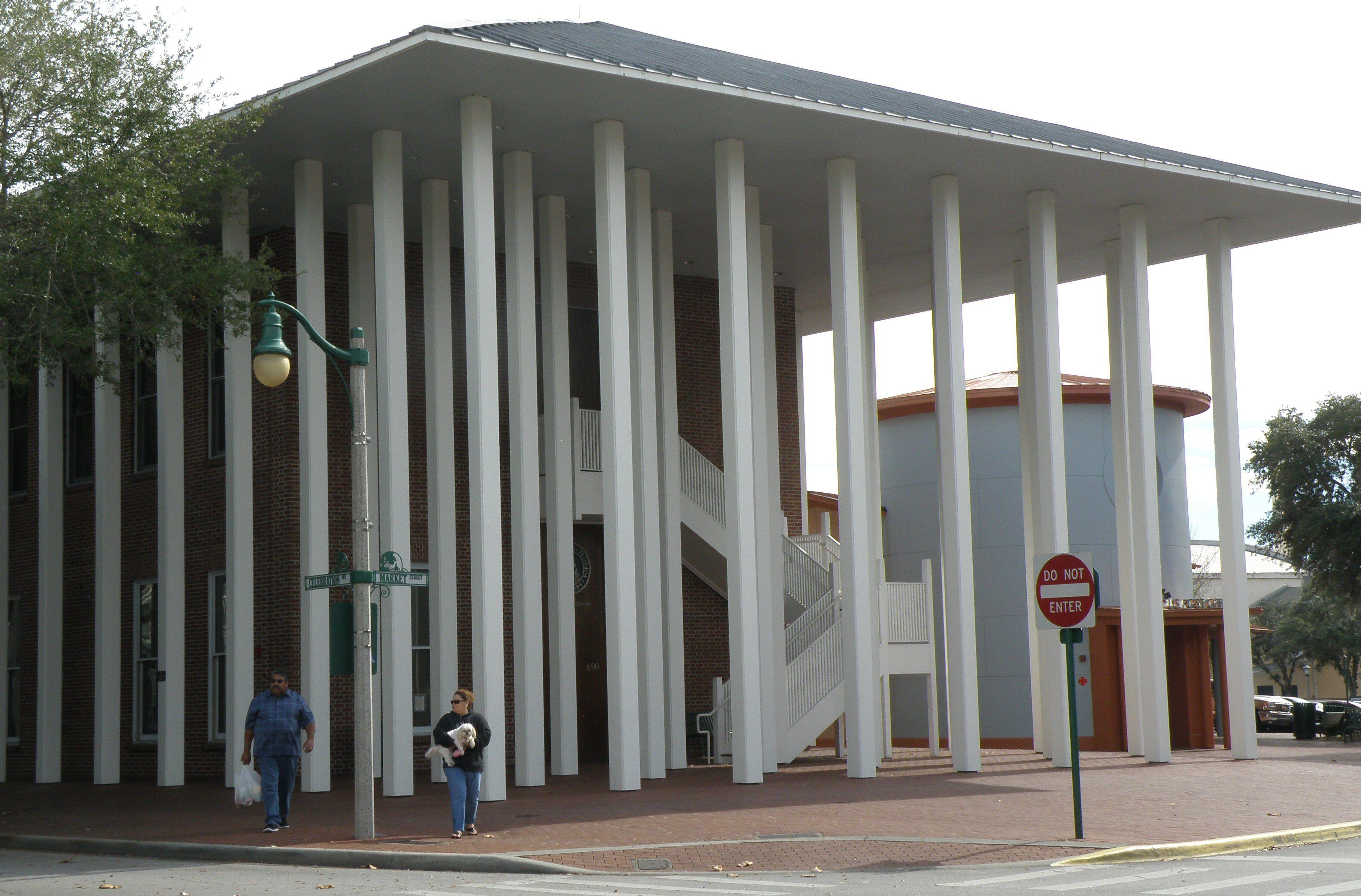 múltiples columnas blancas bajo un techo a cuatro aguas ocultan la entrada a todo el edificio