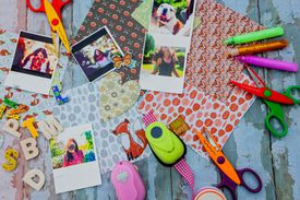 'Assortment of scrapbooking tools including colored paper, pens, and scissors.