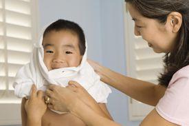 Woman helping a young boy put on a shirt