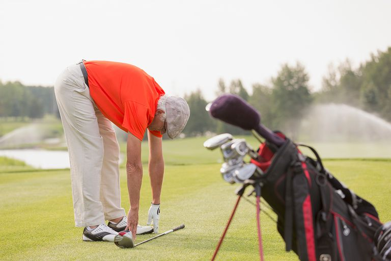 Senior man stretching and touching toes on golf course.