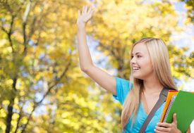student with folders waving hand over autumn park