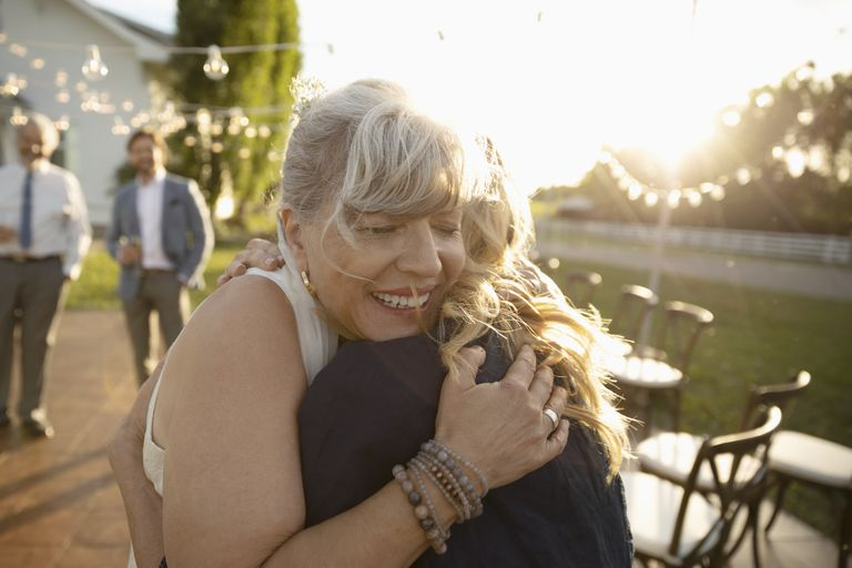 Affectionate senior bride hugging friend in sunny rural garden