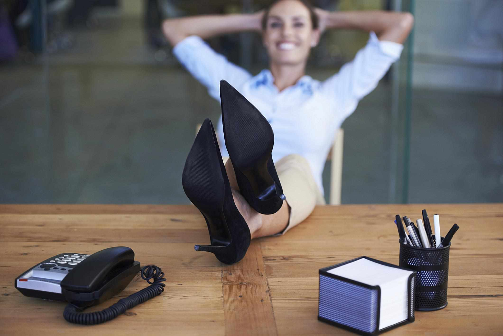 A woman sitting with her legs on a desk