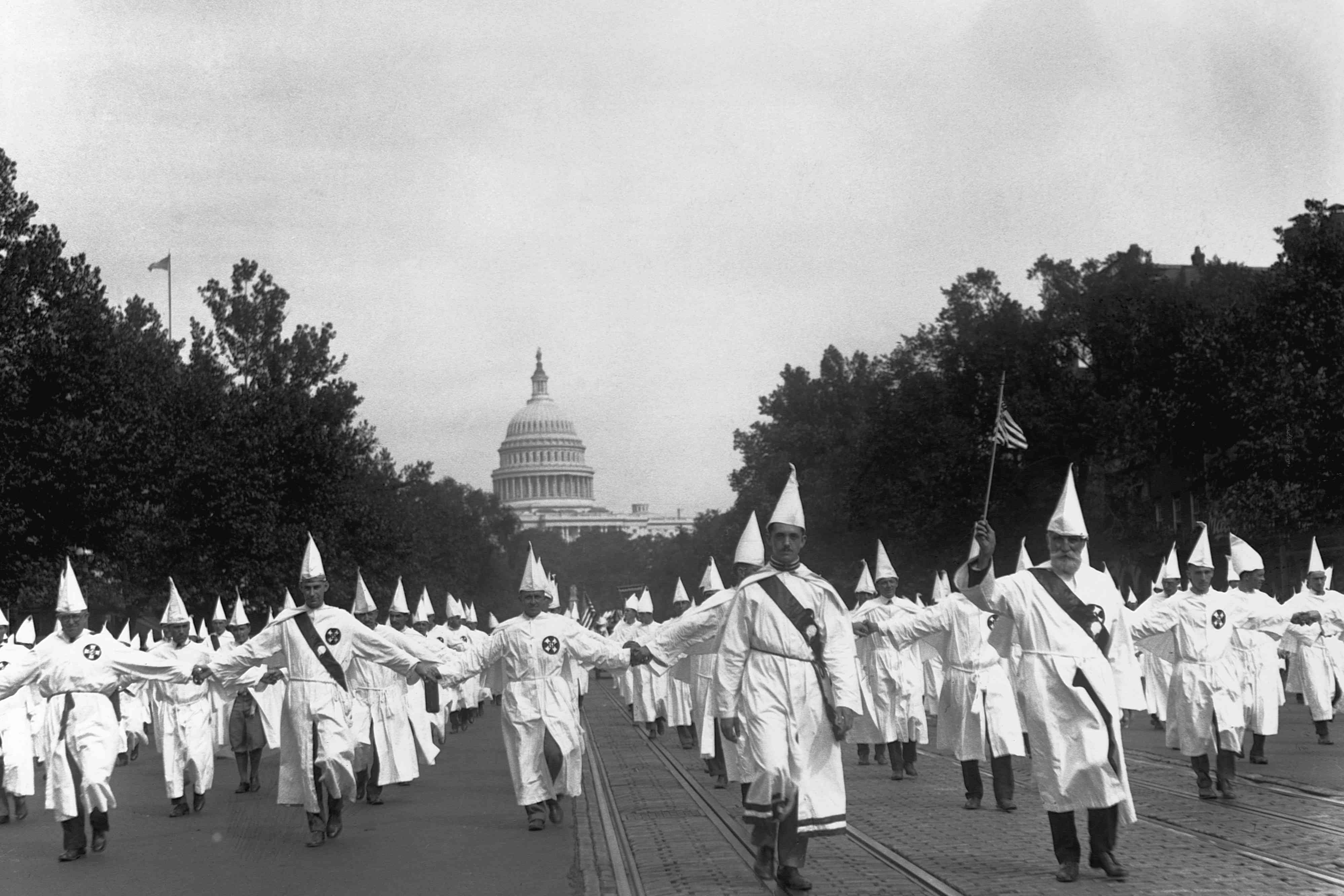 Ku Klux Klan members in hoods and robes walking down the street with the U.S. Capitol Building visible on the horizon