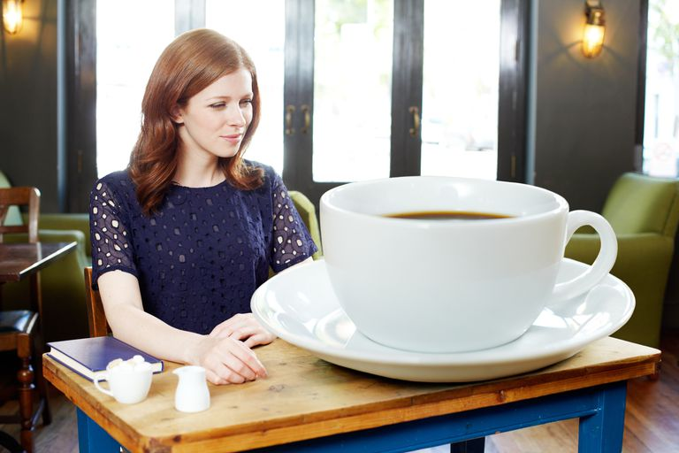 Woman sitting at table with dramatically over-sized cup of coffee