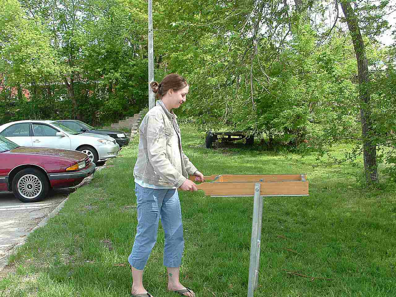 An archaeologist demonstrates the shaker screen (pay no attention to the inappropriate footwear).