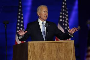 Joe Biden standing at a podium with two flags behind him