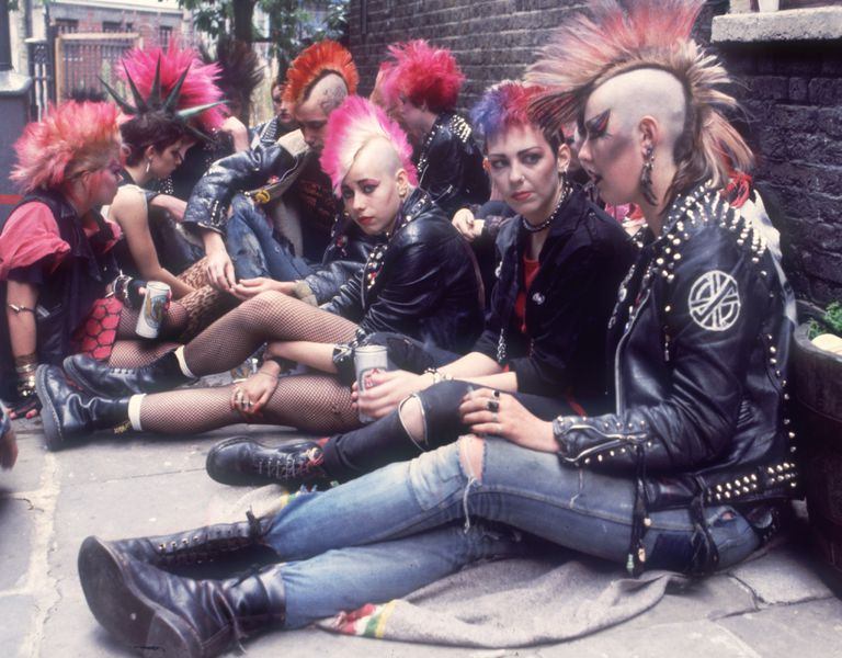 Homeless punks with pink Mohawks of the gutter punk movement sitting on the curb