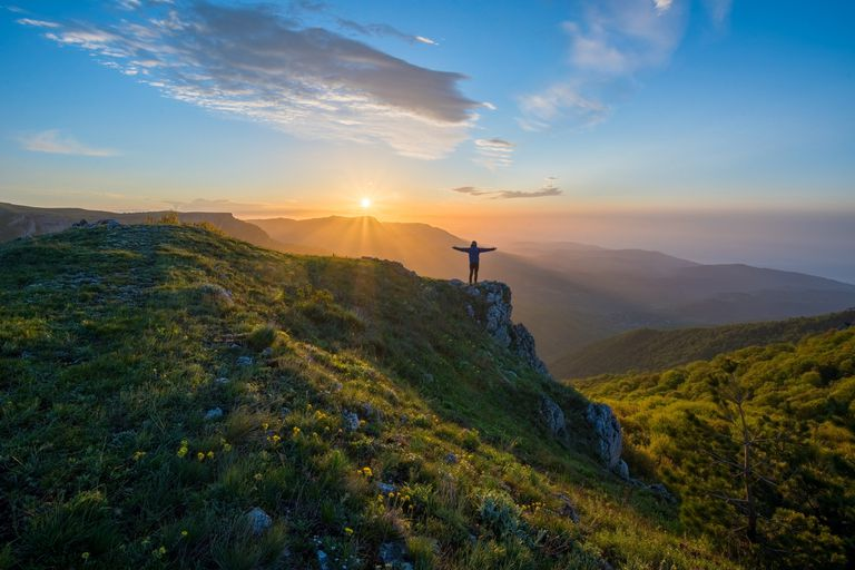 sunrise over a montain top with a person in silhouette with arms out