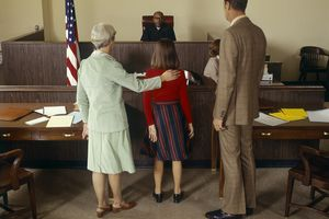 Parents stand with child in courtroom