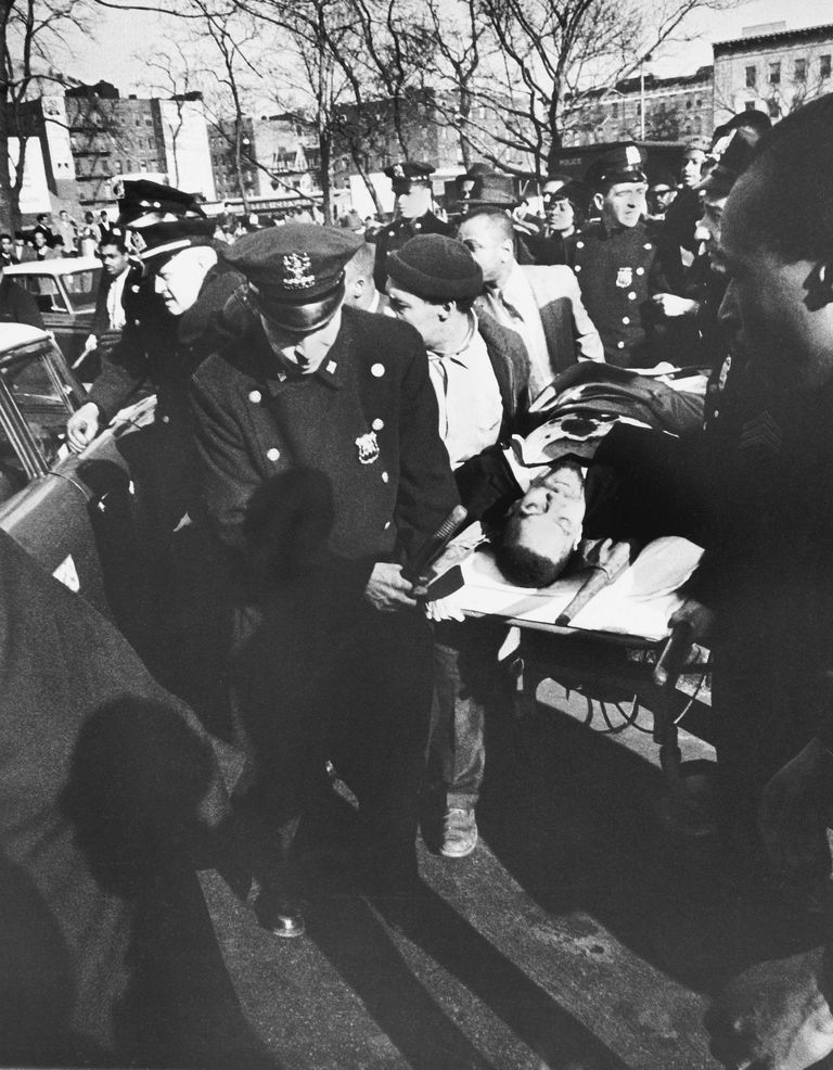 Malcolm X's body being carried on a stretcher after his assassination.