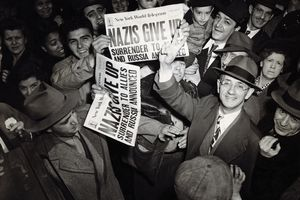 New Yorkers celebrate V-E Day and the end of WWII, holding up newspapers and smiling, black and white photograph.