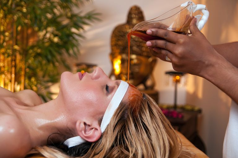 A woman has a soothing Ayurveda massage to her forehead