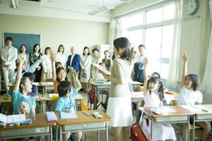 Classroom full of students raising their hands with the teacher at the center.