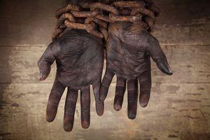 black hands bound in heavy, rusty chains
