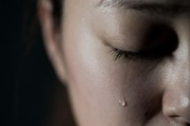 closeup of woman's face with tear