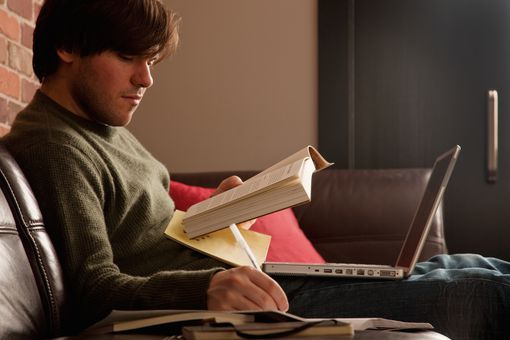 Man writing on paper with book and laptop on lap.