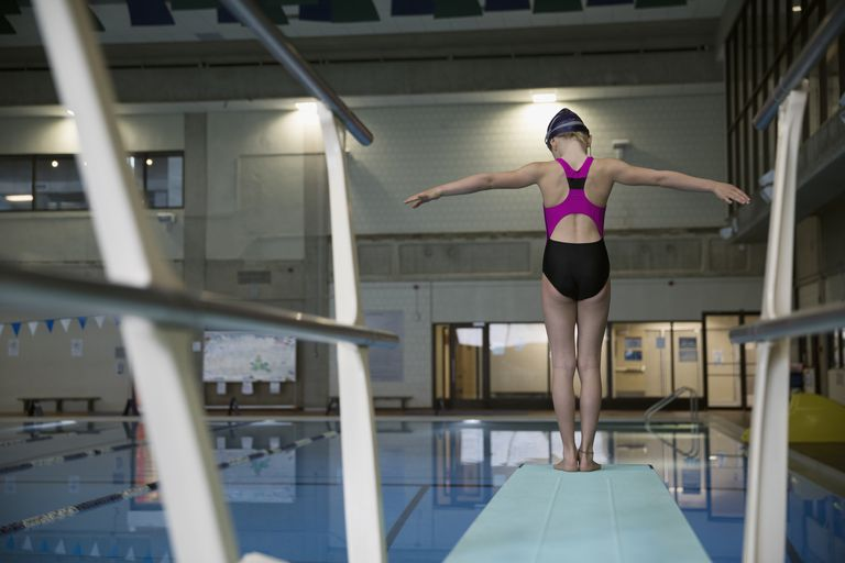 Girl swimmer standing at the edge of springboard diving board over swimming pool