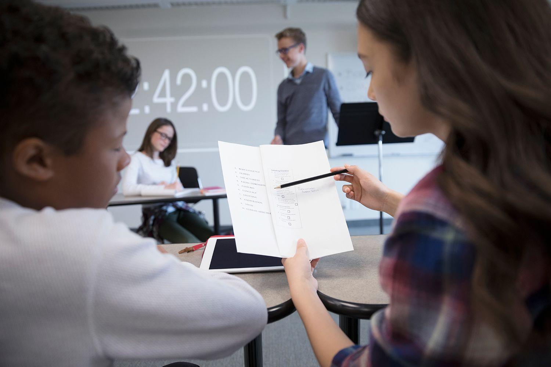 Mittelschüler, die Notizen im Debattenclub im Klassenzimmer betrachten