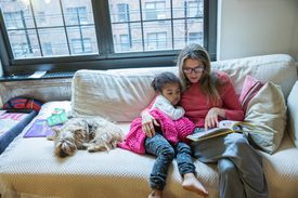 Young girl and her mom reading together on a couch with dog nearby
