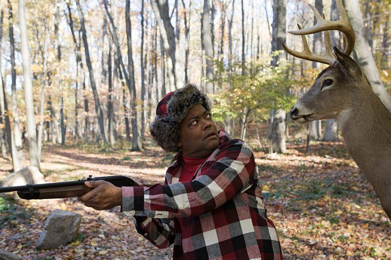 Deer standing behind a hunter