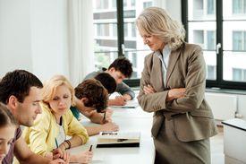 Portrait of confident professor with university students in classroom