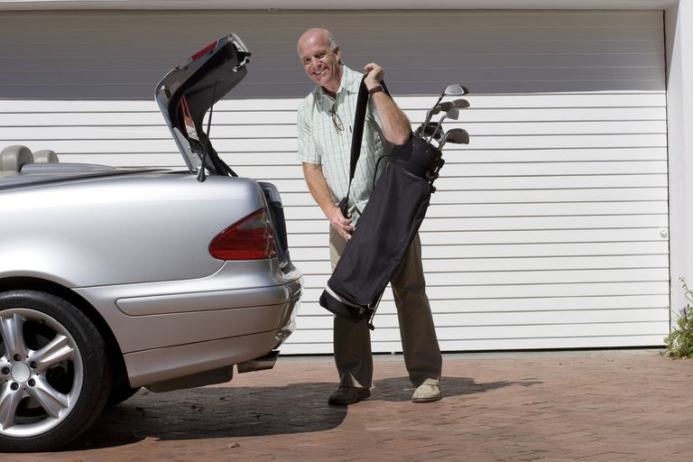Man putting golf clubs in the trunk of his car