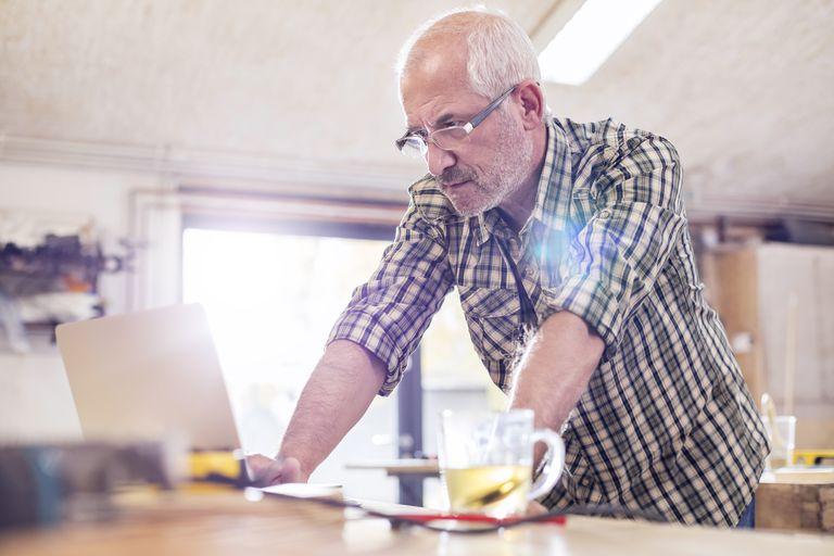 Serious senior male carpenter using laptop in workshop