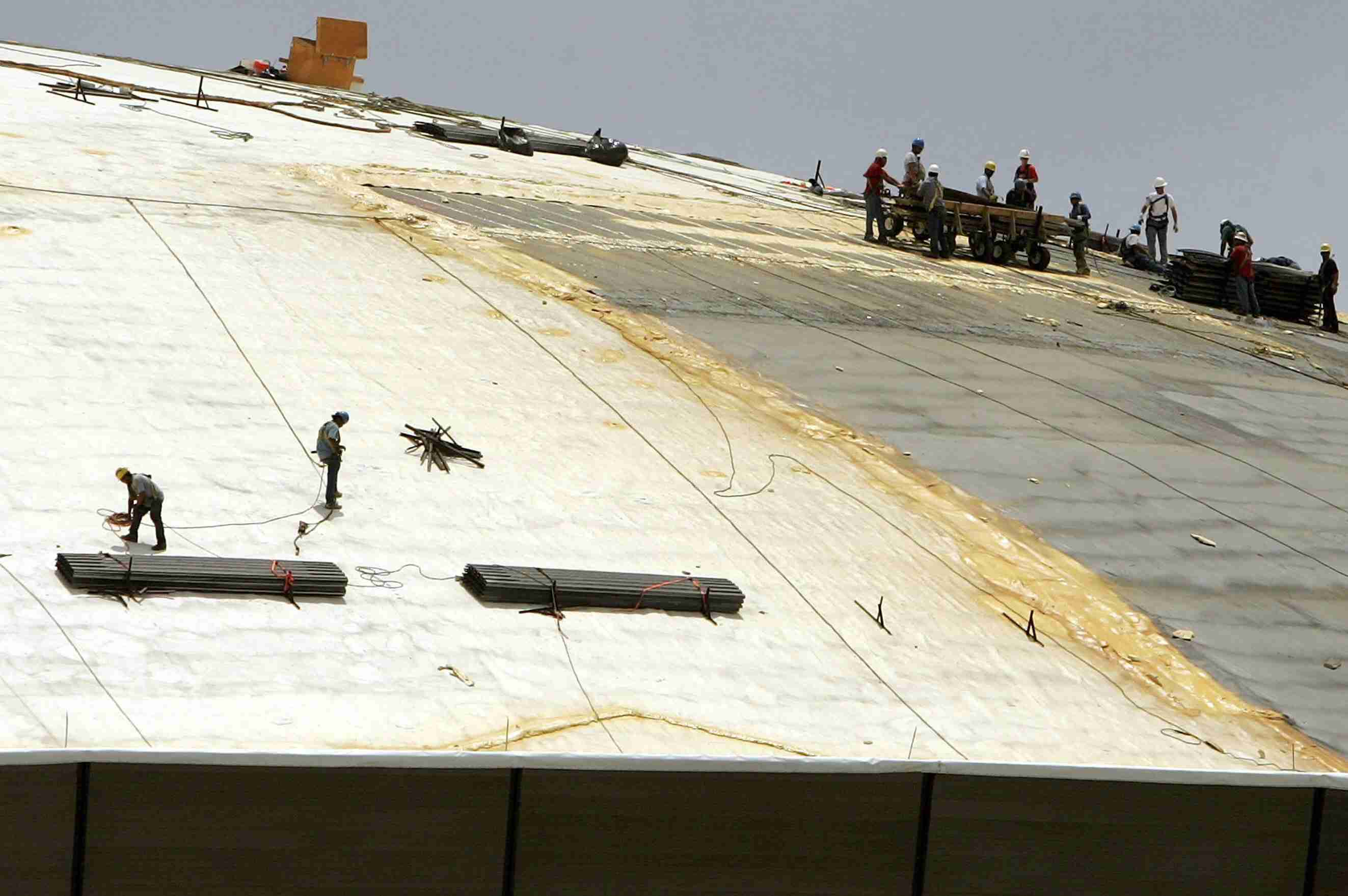 two crews of workers resheathing top of dome