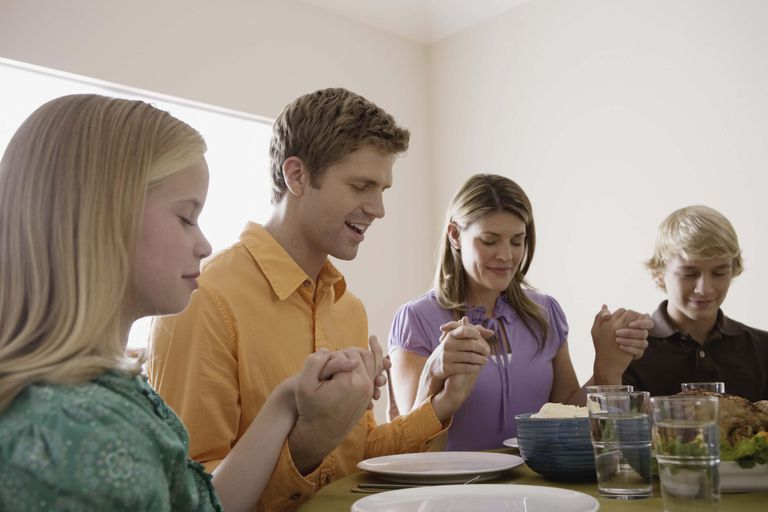 Family holding hands and praying over food at dinner table