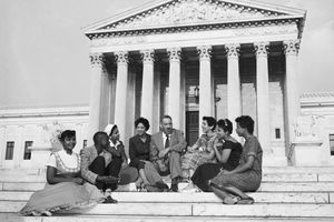 Black lawyer Thurgood Marshall sitting with Little Rock Nine students on the steps of the U.S. Supreme Court building