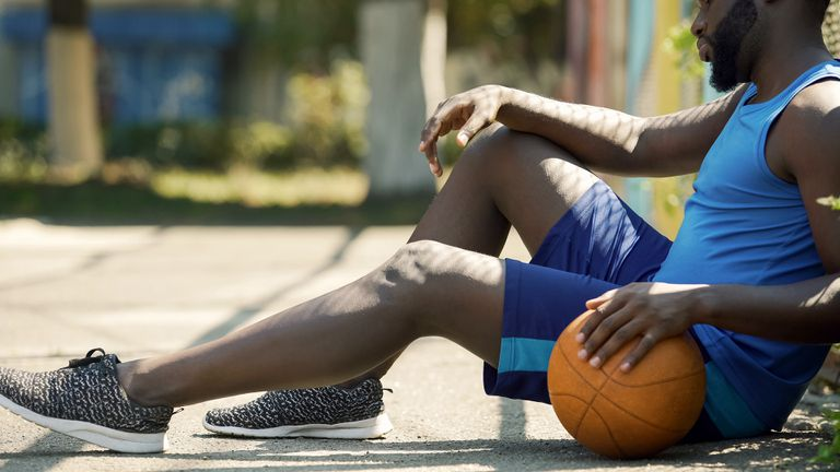 Tired African American basketball player sitting on ground, holding ball