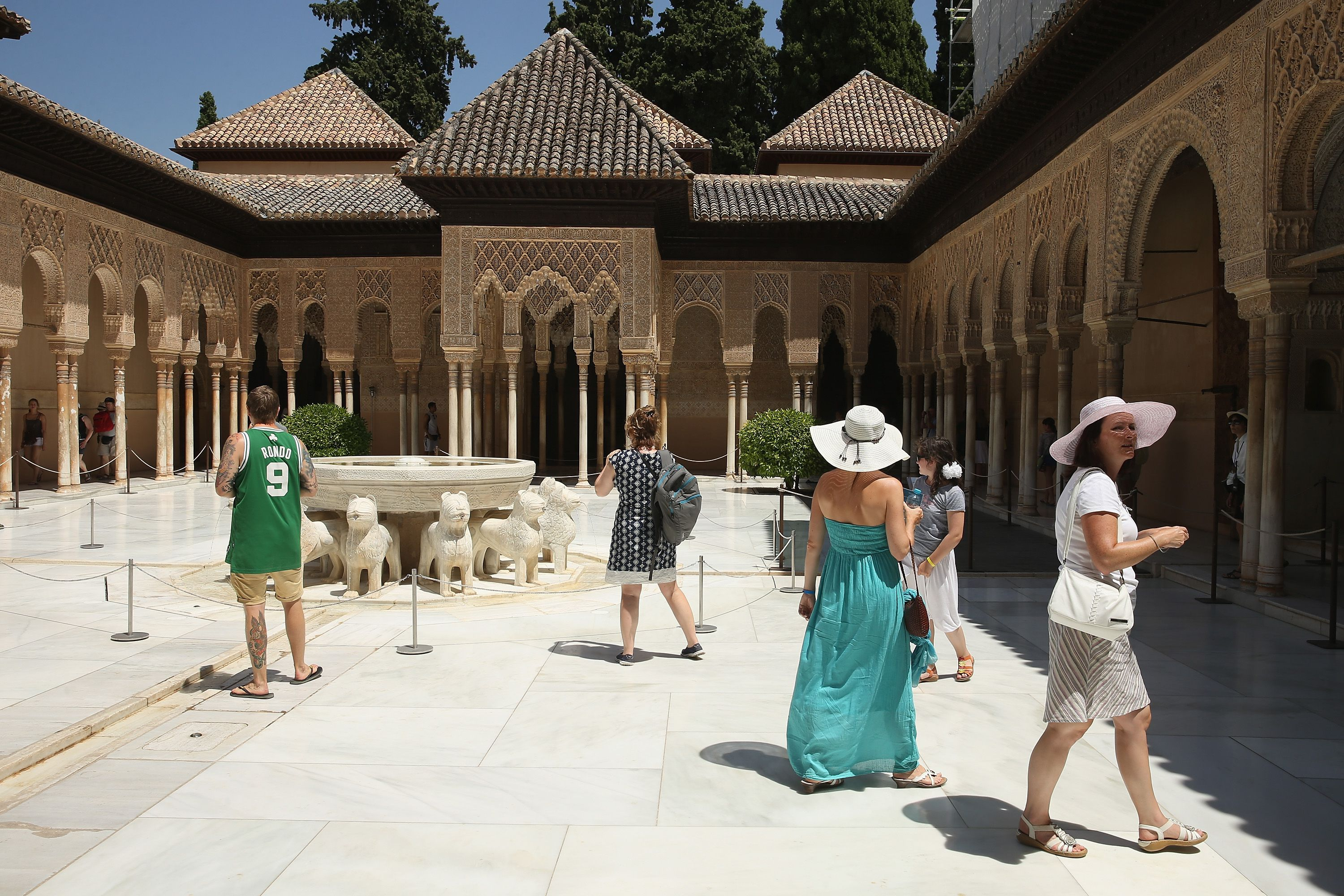courtyard surrounded by carved columns leading to palaces, sculpture fountain with lions in the center, Alhambra Tourists mingle