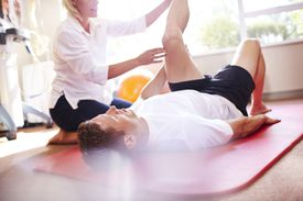 Physical therapist stretching mans leg