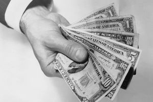Man's hand holding US paper money