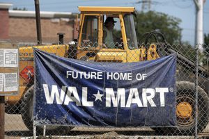 A sign advertising a new Wal-Mart hangs on a chain-link fence near the construction project