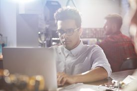 Serious, focused young man working at laptop