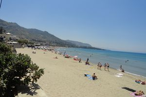Italian beach with people on the sand and in the water under a cloudless blue sky.