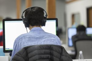 Back of head of male with headphones looking at a computer screen