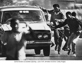Demonstrators chasing a car during Soweto Uprising