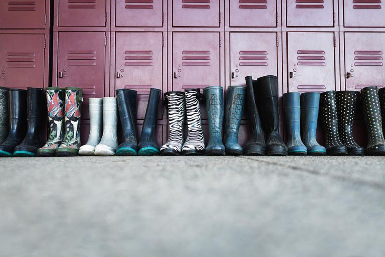 Pairs of rain boots in front of school lockers