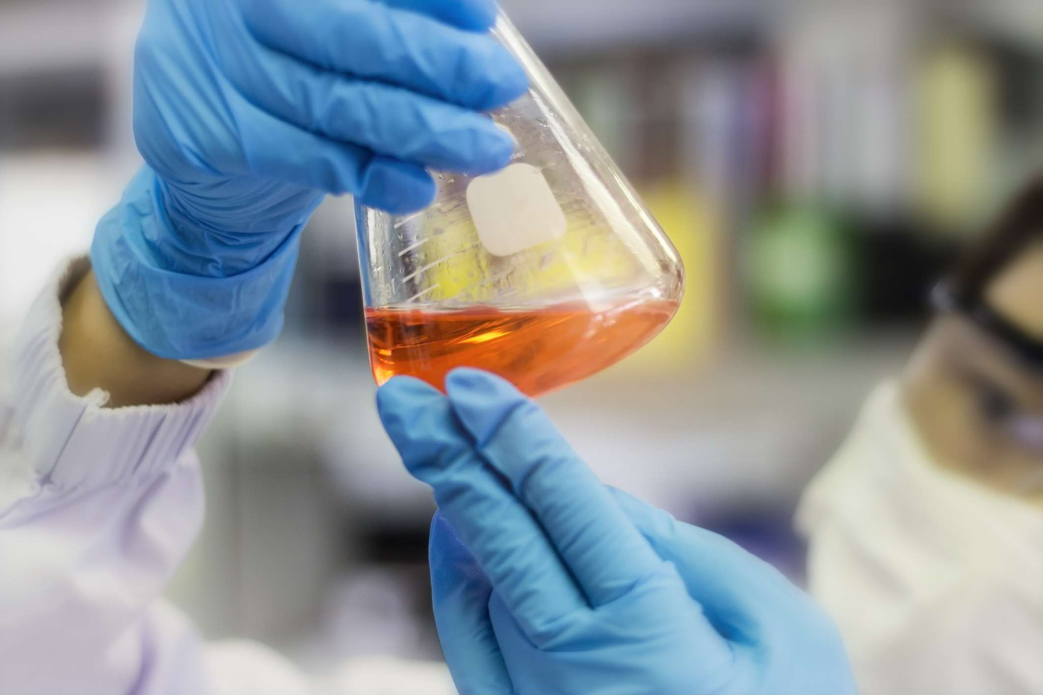 scientist is looking at the reaction of reagent in a flask